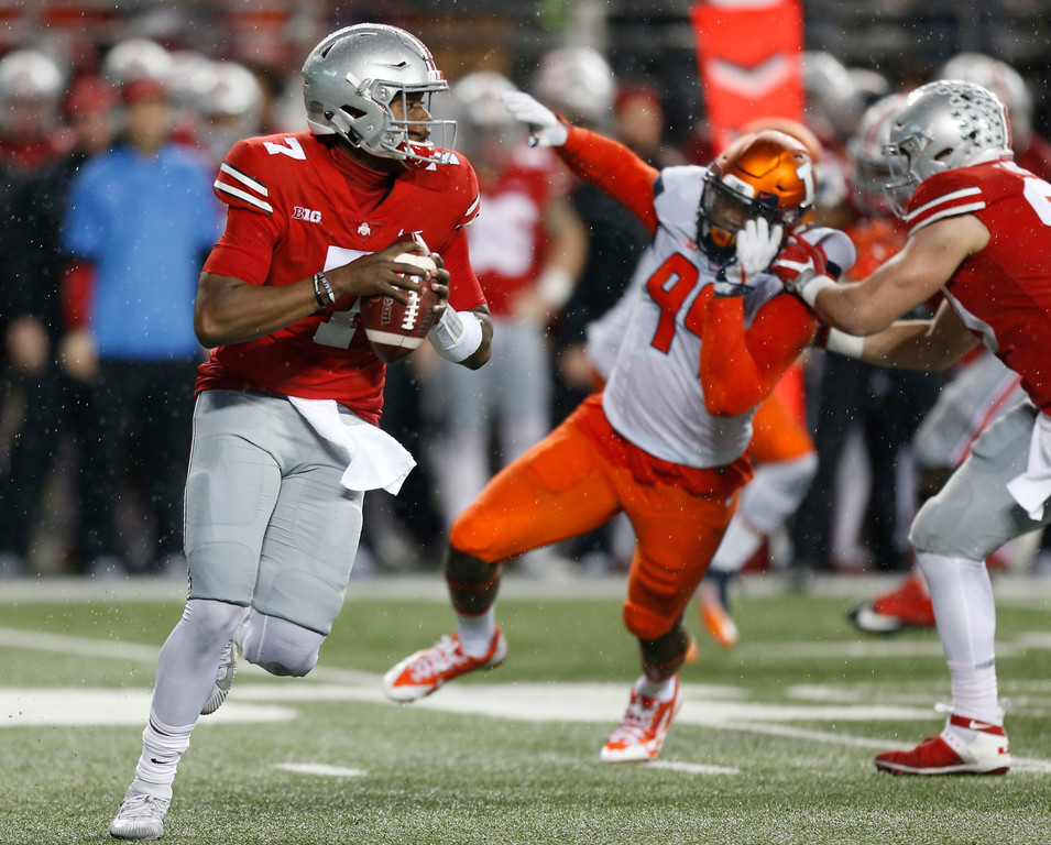 . Ohio State quarterback Dwayne Haskins, left, scrambles in the backfield against Illinois during the second half of an NCAA college football game Saturday, Nov. 18, 2017, in Columbus, Ohio. (AP Photo/Jay LaPrete)