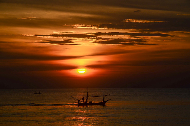 Tropical sunrise seascape with fishing boat, Thailand.