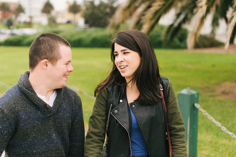Teenage boy with Down Syndrome laughing with a Young Woman of Twenty. with Down Syndrome walking with a Young Woman