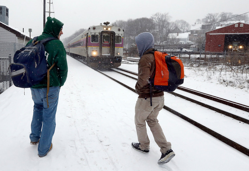 . Two travelers walk to catch the last train into Boston from the Andover, Mass. train station as snow falls on Friday, Feb. 8, 2013. A major winter storm is barreling into the U.S. Northeast with up to 2 feet of snow expected for a Boston-area region that has seen mostly bare ground this winter. The MBTA will suspend all transit service in the late afternoon due to the storm. (AP Photo/Elise Amendola)