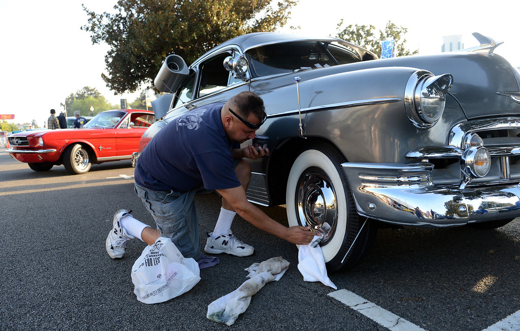 . Andy Braunstein, of West Covina, polishes the hubcaps on his 1950 Chevy at the Route 66 Cruisin\' Reunion on Euclid Ave in Ontario, CA Friday, September 20, 2013. (Jennifer Cappuccio Maher/Inland Valley Daily Bulletin)