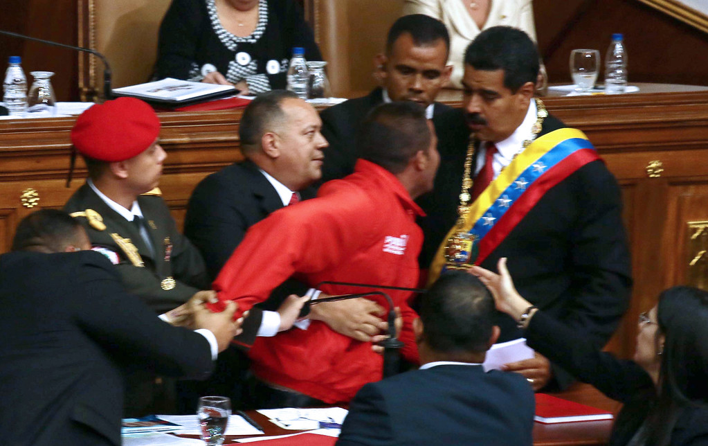 . Venezuelan National Assembly president Diosdado Cabello (C) and security personnel restrain a man (red jacket) who all of a sudden approached Venezuelan President Nicolas Maduro (R) during his inauguration in Caracas, on April 19, 2013.  FRANCISCO BOZA/AFP/Getty Images