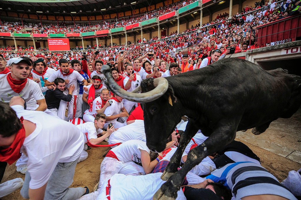 """. A bull jumps over revelers on the bull ring at the San Fermin festival, in Pamplona, Spain, Tuesday, July 8, 2014. Revelers from around the world in Pamplona take part in an eight-day event of the running of the bulls glorified by Ernest Hemingway\'s 1926 novel \""""The Sun Also Rises.\"""" (AP Photo/Alvaro Barrientos, File)"""