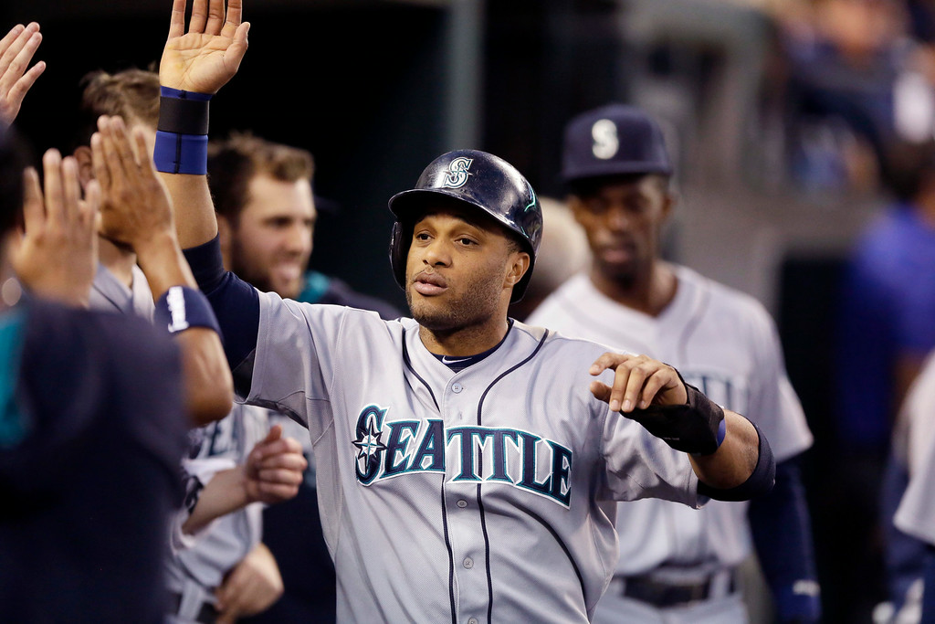 . Seattle Mariners\' Robinson Cano is congratulated in the dugout after scoring during the fifth inning of a baseball game against the Detroit Tigers, Friday, Aug. 15, 2014, in Detroit. (AP Photo/Carlos Osorio)