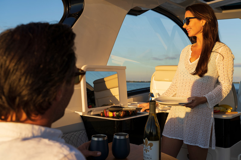 2021-Sundancer-370-Outboard-DAO370-lifestyle-couple-cooking-cockpit-wet-bar-grill-05906.jpg