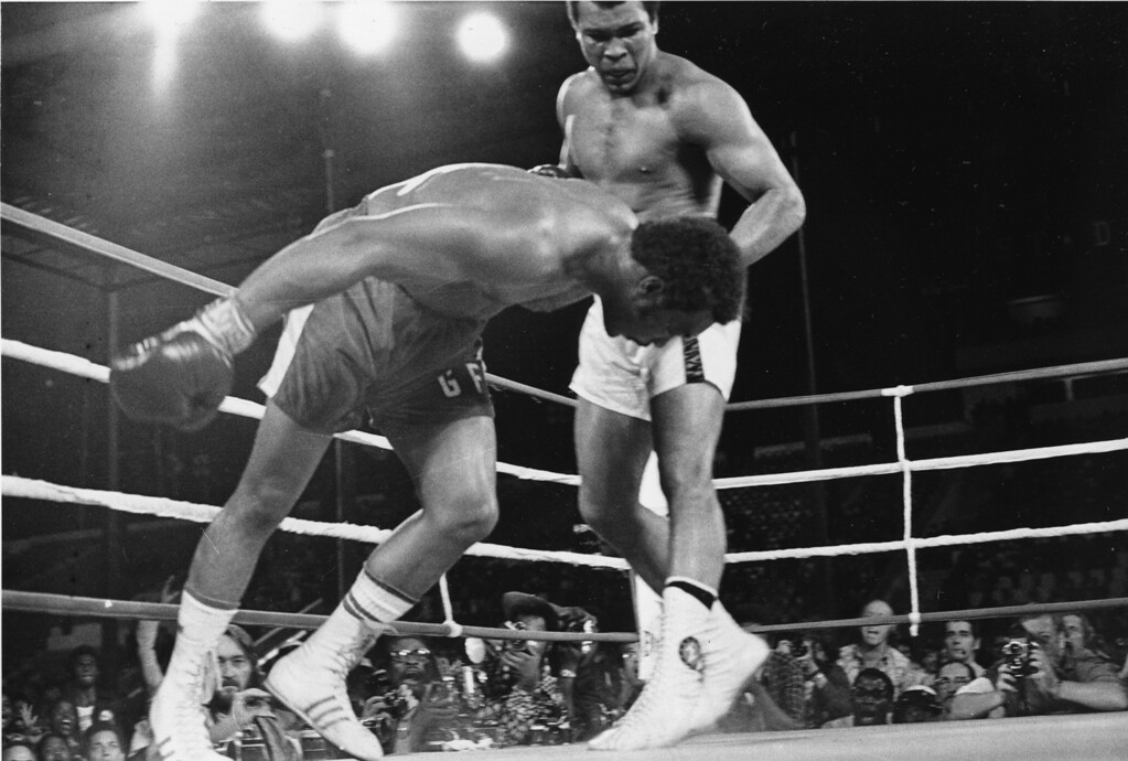 . Challenger Muhammad Ali watches as defending world champion George Foreman goes down to the canvas in the eighth round of their WBA/WBC championship match in Kinshasa, Zaire, on October 30, 1974. Foreman is counted out by the referee and Ali regains the world heavyweight crown by KO in the bout dubbed \'Rumble in the Jungle.\' (AP Photo)