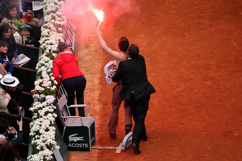 . A security guard restrains a protester after he lit a flare and ran on court before the start of a game in the Men\'s Singles final match between Rafael Nadal of Spain and David Ferrer of Spain during day fifteen of the French Open at Roland Garros on June 9, 2013 in Paris, France.  (Photo by Clive Brunskill/Getty Images)