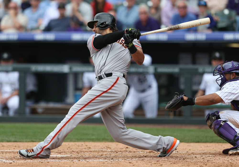 . San Francisco Giants\' Michael Morse lines out with the bases loaded, in front of Colorado Rockies catcher Wilin Rosario during the fifth inning of a baseball game in Denver on Wednesday, April 23, 2014. (AP Photo/David Zalubowski)