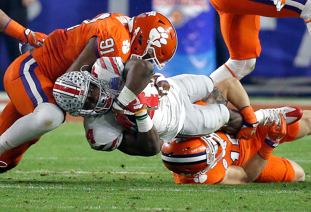 . Ohio State running back Curtis Samuel, center, is tackled by Clemson defensive end Austin Bryant (91) and Tanner Muse during the first half of the Fiesta Bowl NCAA college football playoff semifinal, Saturday, Dec. 31, 2016, in Glendale, Ariz. (AP Photo/Ross D. Franklin)