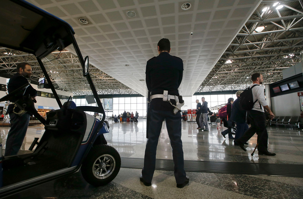 . Police officers patrol the check in area of the Milan\'s Malpensa international airport, in Busto Arsizio, Italy, Tuesday, March 22, 2016. Authorities in Europe have tightened security at airports, on subways, at the borders and on city streets after deadly attacks Tuesday on the Brussels airport and its subway system. (AP Photo/Luca Bruno)
