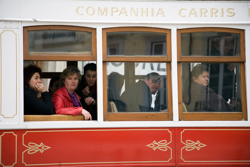 Passengers looking through the window of a city tram, Lisbon