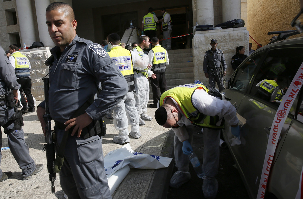 . Israeli emergency services members cleans the side of a car at the scene of an attack, by two Palestinians, on Israeli worshippers at a synagogue in the ultra-Orthodox Har Nof neighborhood in Jerusalem on November 18, 2014. Two Palestinians armed with a gun and axes burst into a Jerusalem synagogue and killed four Israelis before being shot dead, in the deadliest attack in the city in years.AFP PHOTO / GALI TIBBON/AFP/Getty Images