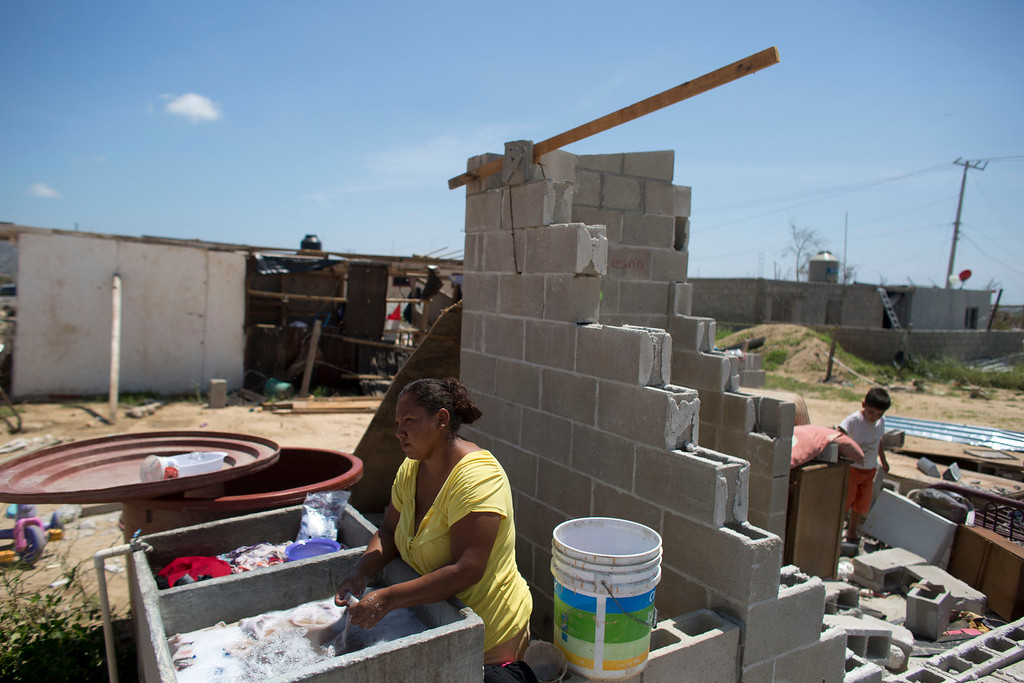 . Maria del Carmen Araiza washes clothes in a concrete wash basin next to what remains of her neighbors\' homes destroyed when Hurricane Odile roared over San Jose de los Cabos, Mexico, Thursday, Sept. 18, 2014. Water and electricity service remained out and phone service was intermittent. Electric commission officials said some 2,500 power poles were toppled by Odile, which struck late Sunday as a Category 3 storm. (AP Photo/Dario Lopez-Mills)