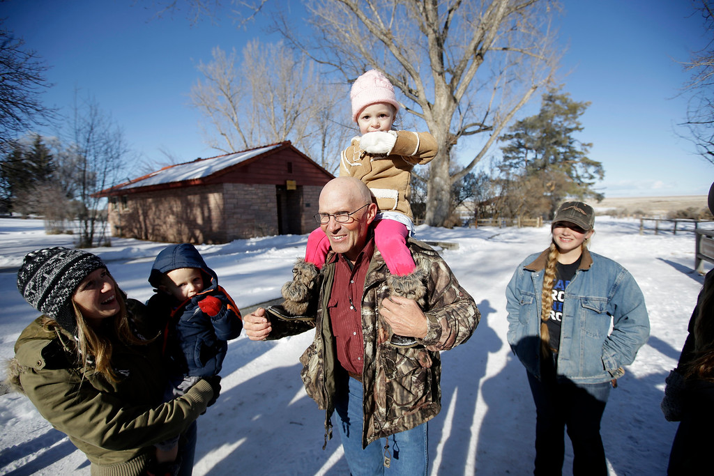 . LaVoy Finicum, center, a rancher from Arizona who is part of an armed group occupying the Malheur National Wildlife Refuge to protest federal land management policies, carries his granddaughter Payton, as other family member watch following a news conference at the refuge Friday, Jan. 8, 2016, near Burns, Ore. Ammon Bundy, the leader of the group said Friday he and his followers are not ready to leave even though the sheriff and many locals say the group has overstayed their welcome.  (AP Photo/Rick Bowmer)