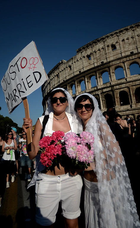 """. A couple dressed as brides holds a placard reading \""""Just married\"""" during the annual gay pride parade in downtown Rome on June 15, 2013. Tens of thousands of people paraded noisily on floats through the historic streets of Rome on June 15 to celebrate Gay Pride, amid calls for Italy to follow France\'s example in legalizing gay marriage.  AFP PHOTO/ FILIPPO  MONTEFORTE/AFP/Getty Images"""