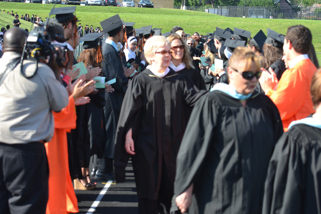. Teachers file through the two columns students formed on the track at the start of the graduation ceremony. Administrators, led by Principal Chuck Baughman, and school district officials also walked between the students. (Photo by Joe Slezak)