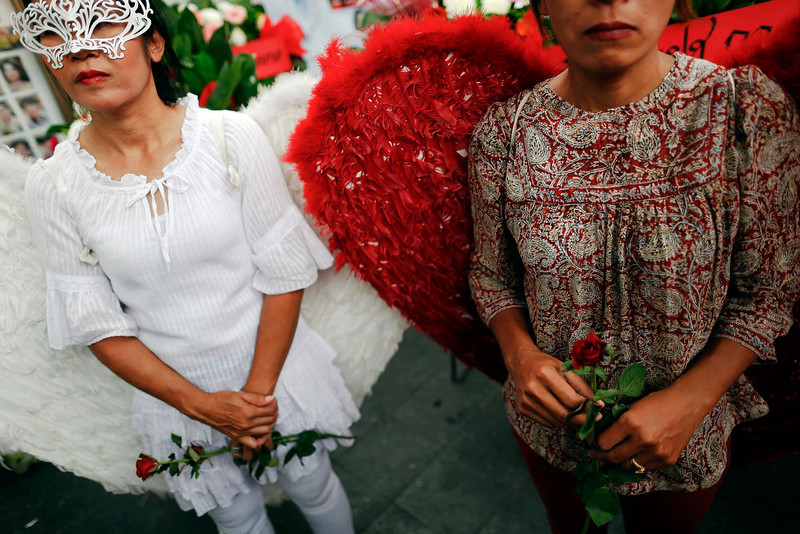 """. Members of the \""""red shirt\"""" movement, dressed as angels hold roses during a gathering near the Democracy Monument, the site of bloody clashes with Thai security forces, in Bangkok on April 10, 2013. Supporters of Thaksin Shinawatra, the former prime minister, and members of the \""""red shirt\"""" movement gathered in Bangkok on Wednesday to mark the third anniversary of bloody clashes and to commemorate their deceased comrades. REUTERS/Damir Sagolj"""