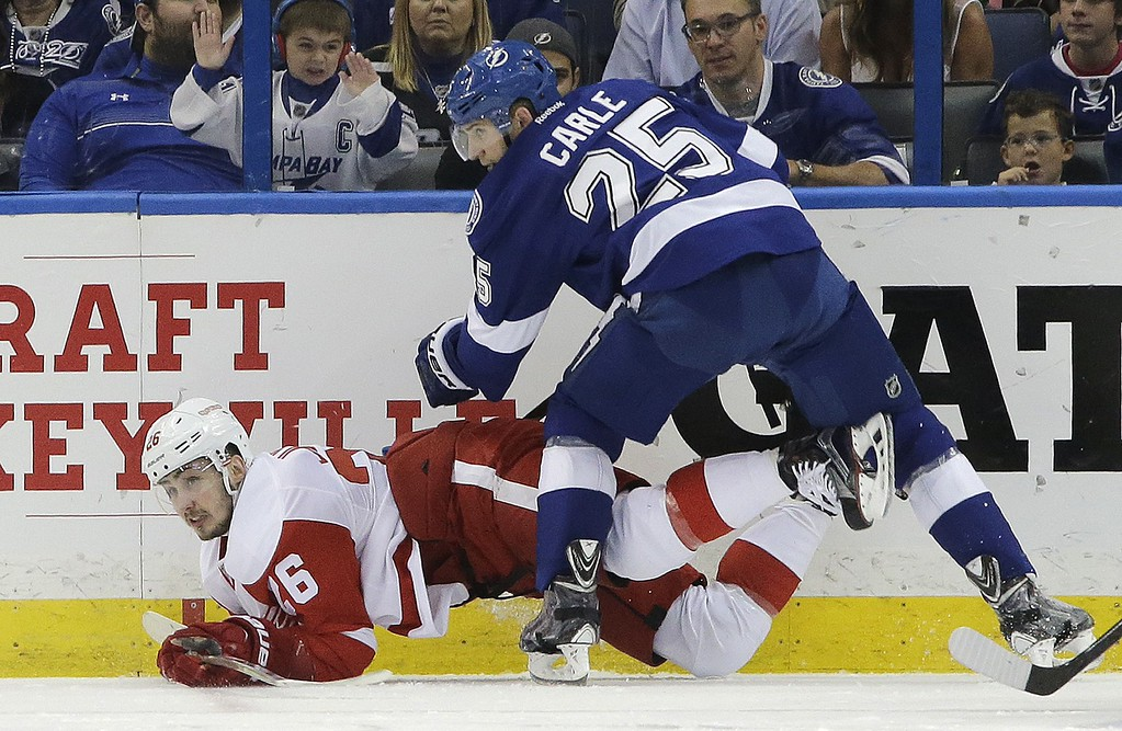 . Tampa Bay Lightning defenseman Matt Carle (25) dumps Detroit Red Wings right wing Tomas Jurco (26), of Slovakia, during the second period of Game 7 of a first-round NHL Stanley Cup hockey playoff series Wednesday, April 29, 2015, in Tampa, Fla. (AP Photo/Chris O\'Meara)