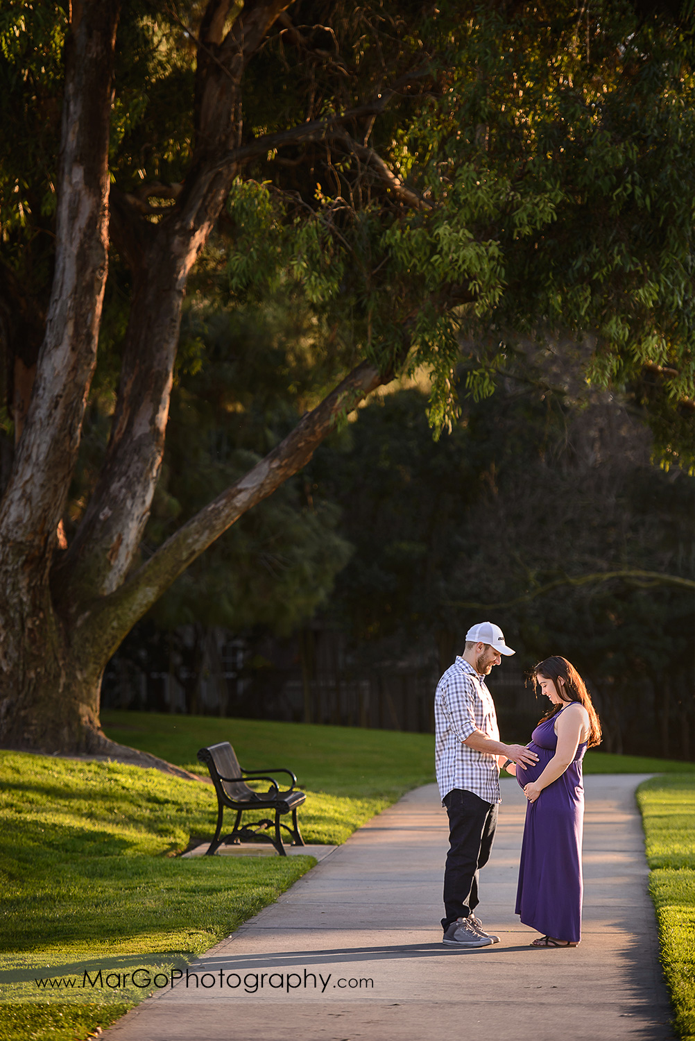 man in checkered shirt and pregnant woman in long violet dress looking at belly during maternity session at Lick Mill Park in Santa Clara