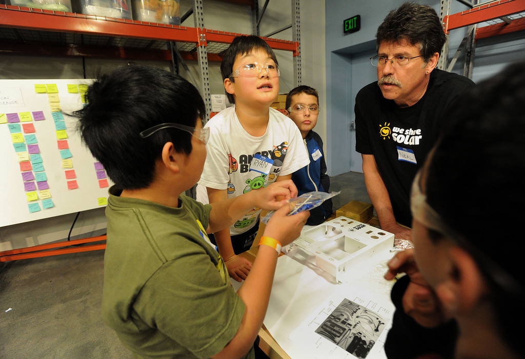 . Ryan Kawahara, center, 11, of Los Altos, checks a white board with assembly information as he and fellow students begin to put together a solar suitcase at the Tech Museum in San Jose, Calif., on Monday, Jan. 21, 2013. As part of Dr. Martin Luther King Jr.\'s legacy of service, young students from around the Bay Area took part in the assembling of WE CARE (Women\'s Emergency Communication and Reliable Electricity) solar suitcases. These suitcases contain a complete solar electric system that will be sent to Sierra Leone, where such kits can be life-changing, bringing light to desperately poor West African schools. The Tech Museum of Innovation is a partner in this program with WE CARE. (Dan Honda/Staff)