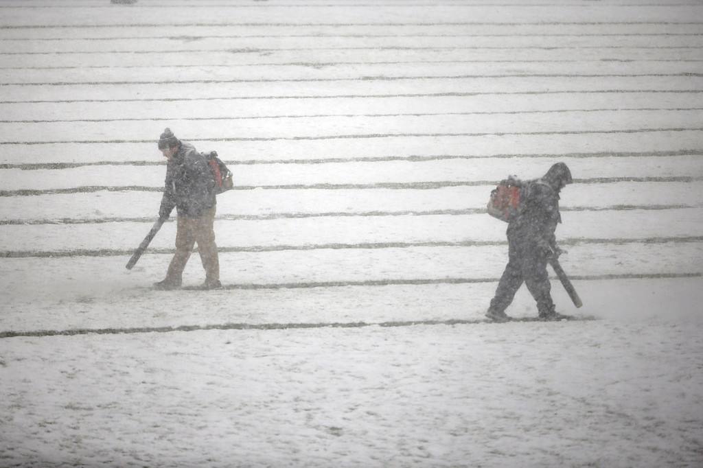 . Philadelphia Eagles personnel clear snow before an NFL football game between the Philadelphia Eagles and the Detroit Lions, Sunday, Dec. 8, 2013, in Philadelphia. (AP Photo/Matt Rourke)
