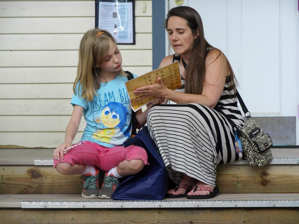 . Maggie Feldkamp and her mom decode the clue that tells where the treasure chest is hidden during a program at Mentor Public Library. (Courtesy Mentor Public Library)