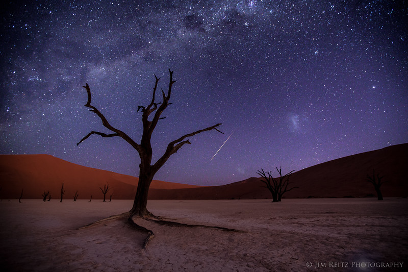 The Milky Way visible over the Deadvlei salt pan in Namibia. This is one frame of 450 shot overnight as raw material for startrail and timelapse photography. This particular frame captured an especially bright meteor.