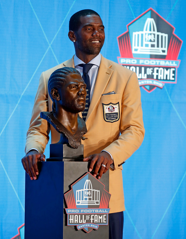 . Former NFL player Randy Moss poses with a bust of himself during an induction ceremony at the Pro Football Hall of Fame, Saturday, Aug. 4, 2018 in Canton, Ohio. (AP Photo/Ron Schwane)