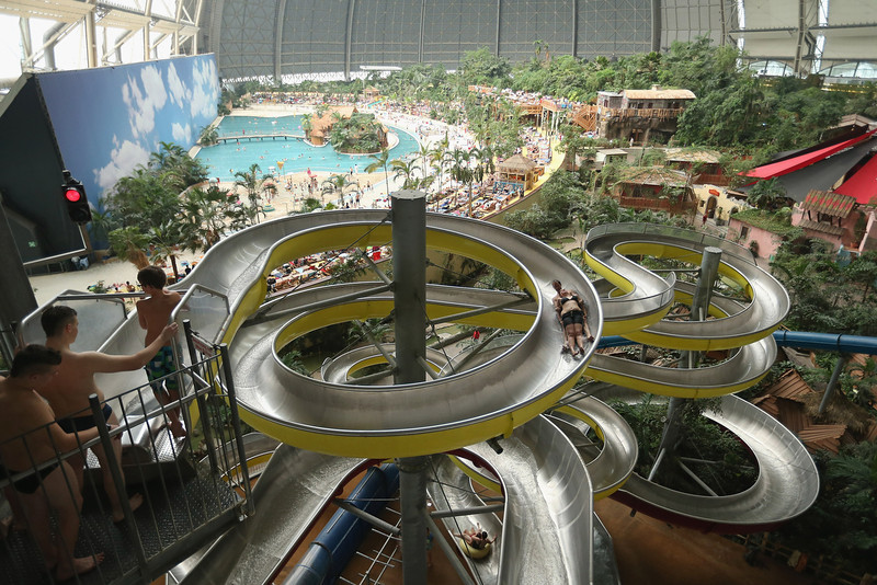 . Visitors slide down the water slide at the Tropical Islands indoor resort on February 15, 2013 in Krausnick, Germany. Located on the site of a former Soviet military air base, the resort occupies a hangar built originally to house airships designed to haul long-distance cargo. Tropical Islands opened to the public in 2004 and offers visitors a tropical getaway complete with exotic flora and fauna, a beach, lagoon, restaurants, water slide, evening shows, sauna, adventure park and overnights stays ranging from rudimentary to luxury. The hangar, which is 360 metres long, 210 metres wide and 107 metres high, is tall enough to enclose the Statue of Liberty.  (Photo by Sean Gallup/Getty Images)