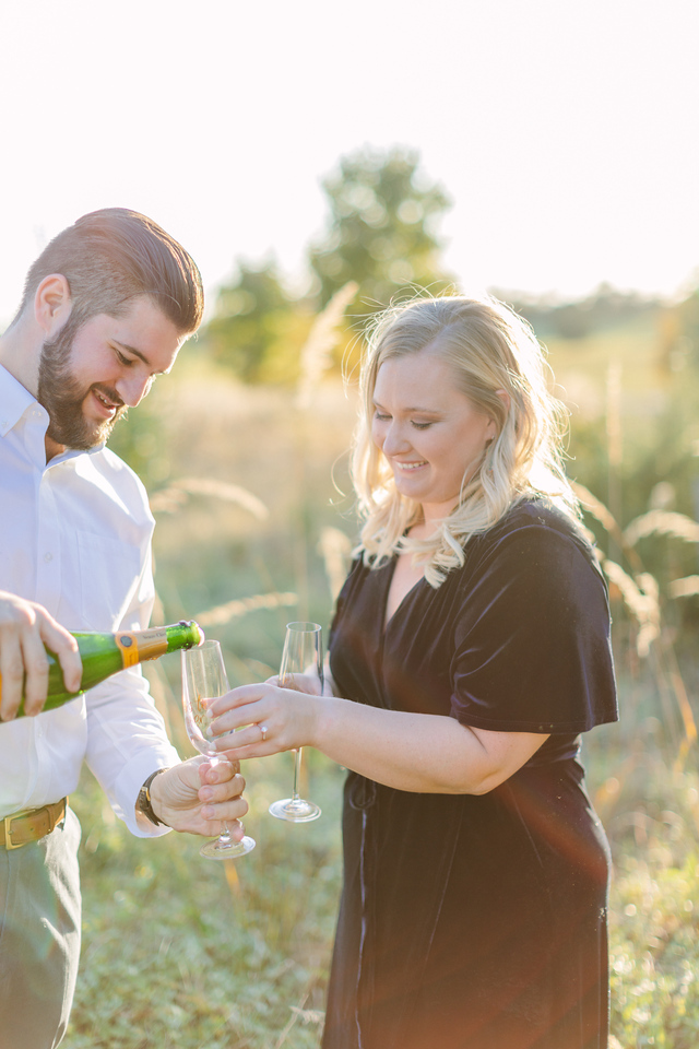 Pouring champagne at their field engagement session in Virginia.