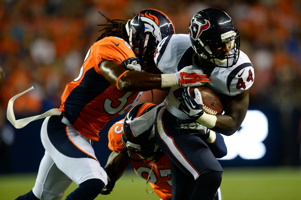 . DENVER, CO - AUGUST 23:  Alfred Blue (44) of the Houston Texans is brought down by Quinton Carter (38) of the Denver Broncos during a preseason football game at Sports Authority Field at Mile High on Saturday, August 23, 2014 in Denver, Colorado.  (Photo by Kent Nishimura/The Denver Post)