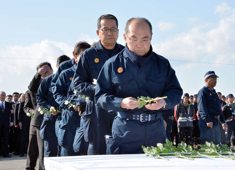 . Police officers offer chrysanthemums for tsunami victims in Namie, near the stricken TEPCO Fukushima Dai-ichi nuclear plant in Fukushima prefecture on March 11, 2014 on the third anniversary day of the massive earthquake and tsunami that hit northern Japan. The 9.0 magnitude earthquake in 2011 sent a huge wall of water into the coast of the Tohoku region, splintering whole communities, ruining swathes of prime farmland and killing nearly 19,000 people. (YOSHIKAZU TSUNO/AFP/Getty Images)