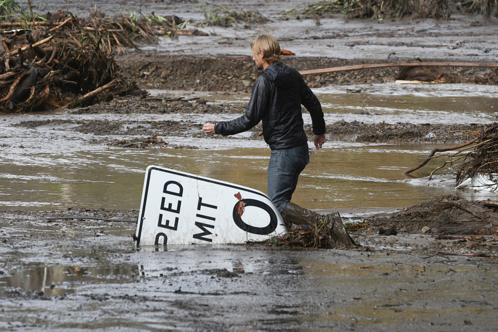 . Phillip Harnsberger crosses through mud from a flooded creek on Sheffield Drive in Montecito, Calif., following heavy rain, Tuesday, Jan. 9, 2018. Multiple people were killed and homes were torn from their foundations Tuesday as downpours sent mud and boulders roaring down hills stripped of vegetation by a gigantic wildfire that raged in Southern California last month. (AP Photo/Michael Owen Baker)