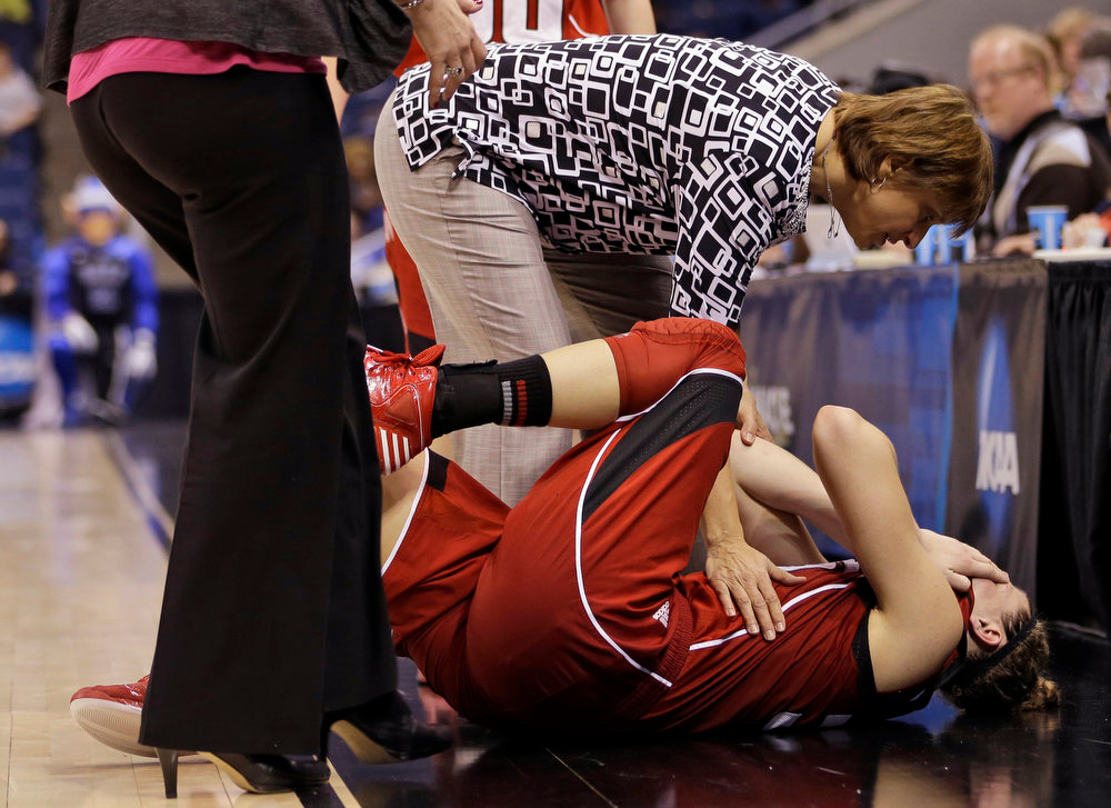 Description of . Nebraska head coach Connie Yori tends to forward Jordan Hooper after Hooper suffered an injury during the second half of a regional semifinal in the women\'s NCAA college basketball tournament against Duke, Sunday, March 31, 2013, in Norfolk, Va. (AP Photo/Steve Helber)