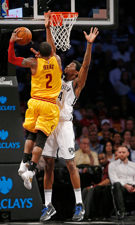 . Brooklyn Nets center Henry Sims (14) defends Cleveland Cavaliers guard Kyrie Irving (2) in the second half of an NBA basketball game, Thursday, March 24, 2016, in New York. The Nets upset the Cavaliers 104-95. (AP Photo/Kathy Willens)