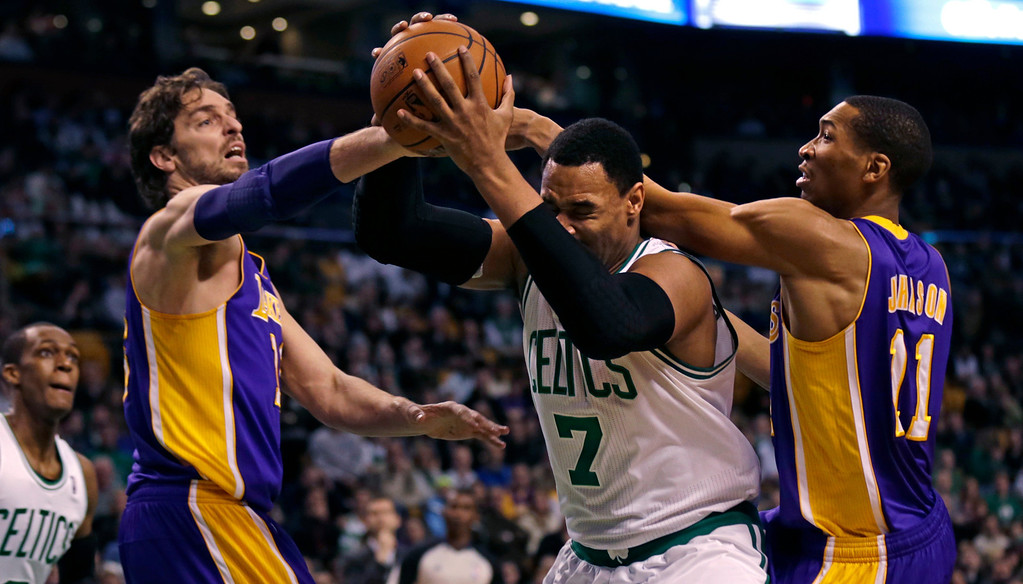 . Los Angeles Lakers center Pau Gasol, front left, and forward Wesley Johnson, right, pressure Boston Celtics forward Jared Sullinger (7) on a rebound during the first quarter of an NBA basketball game in Boston, Friday, Jan. 17, 2014. (AP Photo/Charles Krupa)