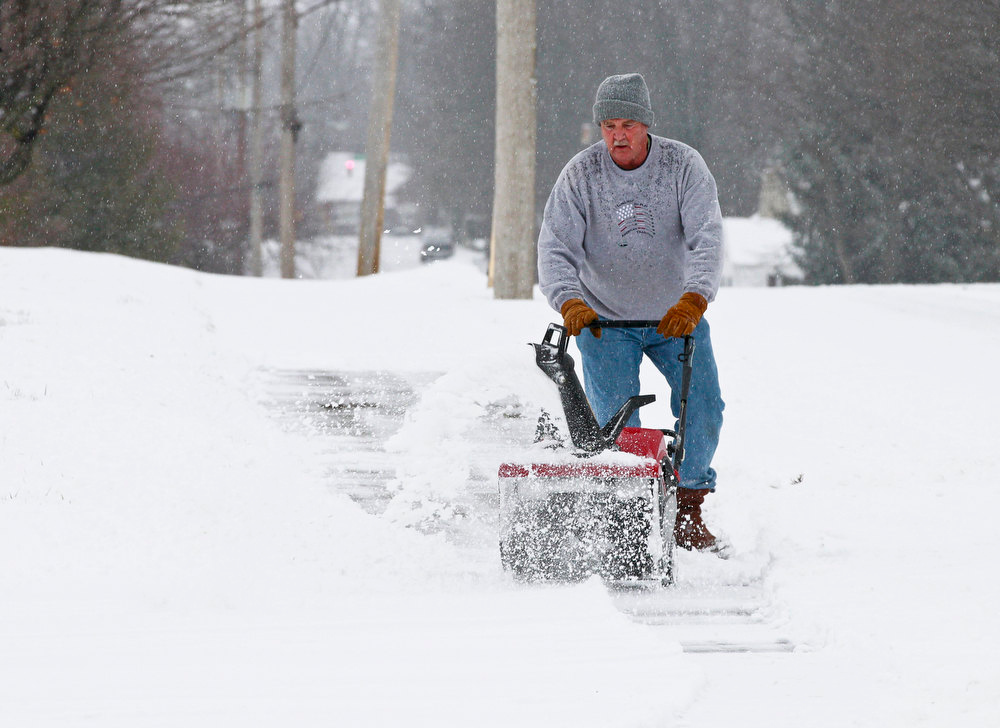 Description of . Nick Aneisley uses a snow blower to clear the sidewalk near his house at Plum and First Streets in Springfield, Ohio, Wednesday, Dec. 26, 2012. (AP Photo/The Springfield News-Sun, Barbara J. Perenic)