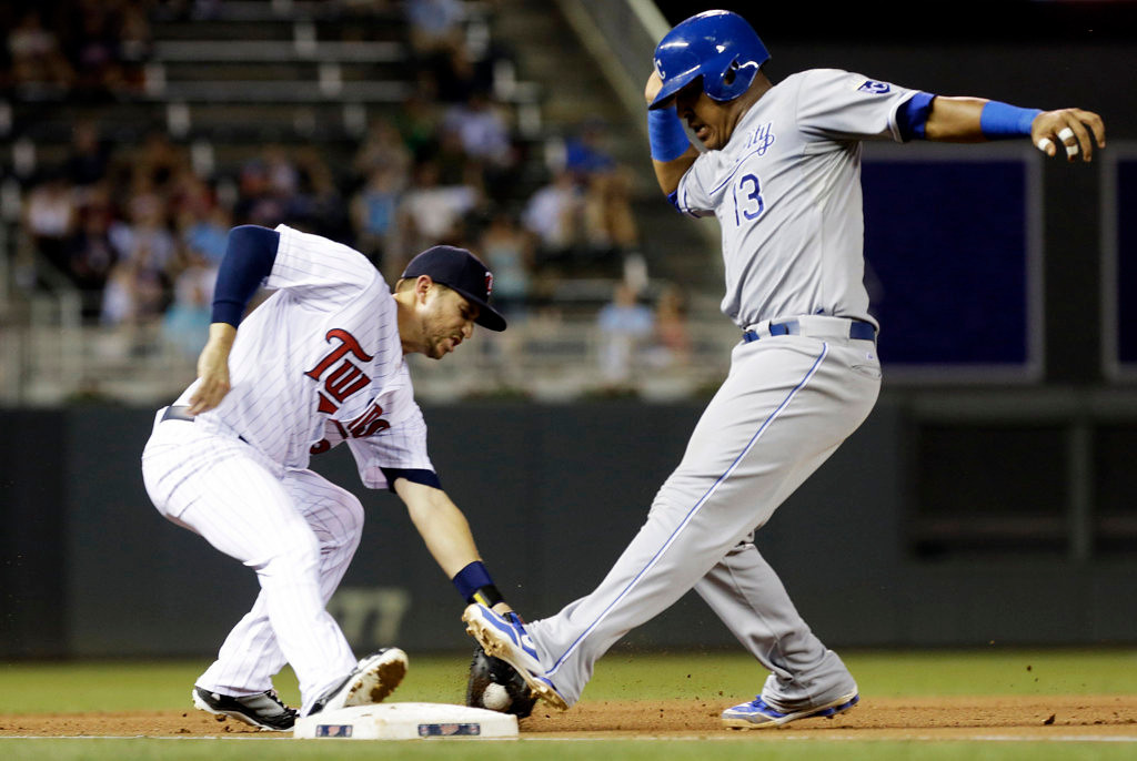 . Minnesota Twins third baseman Trevor Plouffe, left, tries to grab the ball on a sharp grounder by Kansas City Royals\' Alcides Escobar as Salvador Perez, right, reaches third base safely in the fourth inning.(AP Photo/Jim Mone)