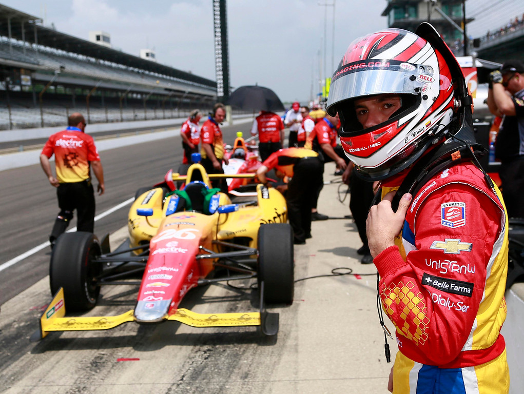 . Andretti Autosport driver Carlos Munoz (R) of Colombia walks toward his race car during a practice session at the Indianapolis Motor Speedway in Indianapolis, Indiana May 16, 2013. The 97th running of the Indianapolis 500 is scheduled for May 26.  REUTERS/Brent Smith