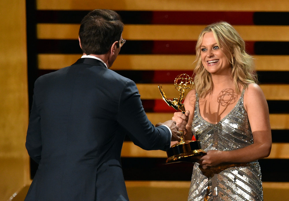 . Actor Ty Burrell (L) accepts Outstanding Supporting Actor in a Comedy Series for \'Modern Family\' from actress Amy Poehler onstage at the 66th Annual Primetime Emmy Awards held at Nokia Theatre L.A. Live on August 25, 2014 in Los Angeles, California.  (Photo by Kevin Winter/Getty Images)