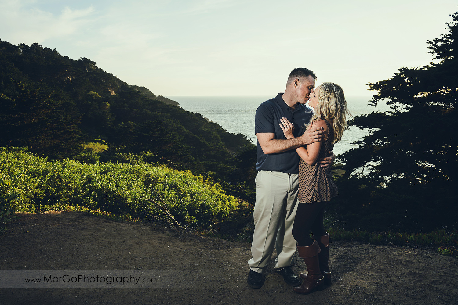 man in navy blue shirt and woman in brown tunic kissing during engagement session at San Francisco Lands End