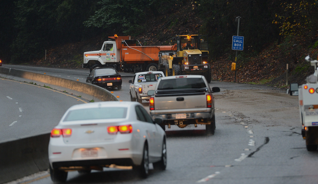 . Crews work to clear a think sheet of mud off of the southbound lanes of Highway 17 near in Los Gatos, Calif., on Thursday, Dec. 11, 2014. The big storm made it way south, after pounding the North Bay in the early morning hours. (Dan Honda/Bay Area News Group)