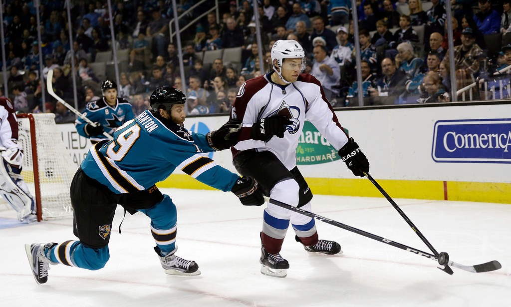 . San Jose Sharks center Joe Thornton (19) lunges for the puck next to Colorado Avalanche defenseman Erik Johnson (6) during the first period of an NHL hockey game in San Jose, Calif., Saturday, Jan. 26, 2013. (AP Photo/Marcio Jose Sanchez)
