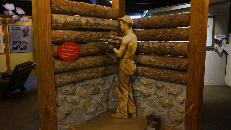 Cutout of young man building a palm log wall in museum display