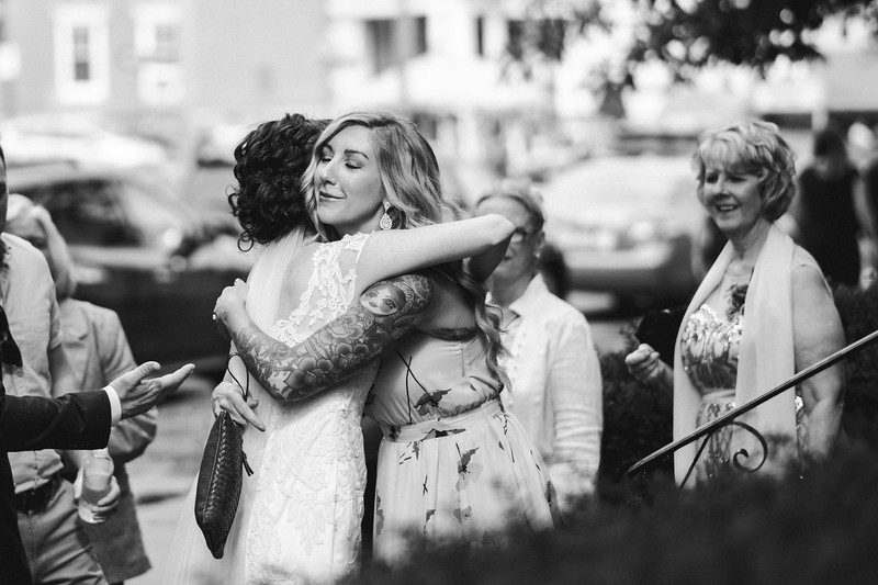 A heavily tattooed woman embraces the bride with a big smile on the steps of the church.