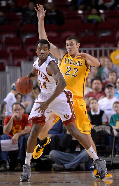 . Denver Pioneers forward Chris Udofia (34) puts a spin move on Wyoming Cowboys forward Larry Nance Jr. (22) during he first half December 15, 2013 Magness Arena. (Photo by John Leyba/The Denver Post)