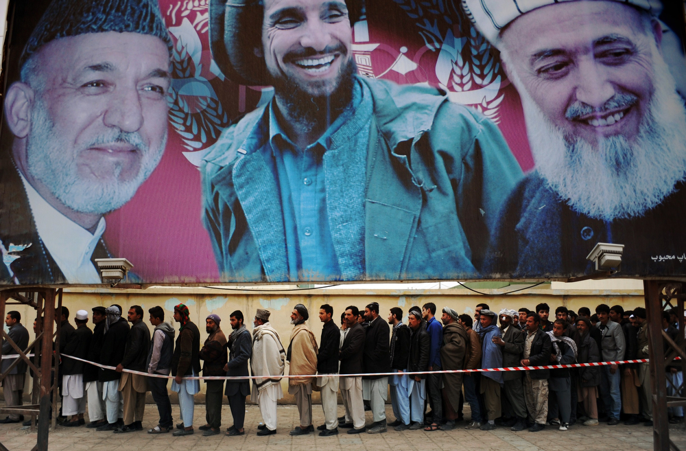 . Afghan residents wishing to vote line up underneath a billboard showing images of Afghan President Hamid Karzai (L) and of deceased Afghan figures Burhandin Rabani (R) and Ahmad Shah Massoud (C) outside a polling station in Mazar-i-Sharif on April 5, 2014. Afghan voters went to the polls Saturday to choose a successor to President Hamid Karzai, braving Taliban threats in a landmark election held as US-led forces wind down their long intervention in the country. Afghanistan\'s third presidential election brings an end to 13 years of rule by Karzai, who has held power since the Taliban were ousted in a US-led invasion in 2001, and will be the first democratic handover of power in the country\'s turbulent history.  (FARSHAD USYAN/AFP/Getty Images)