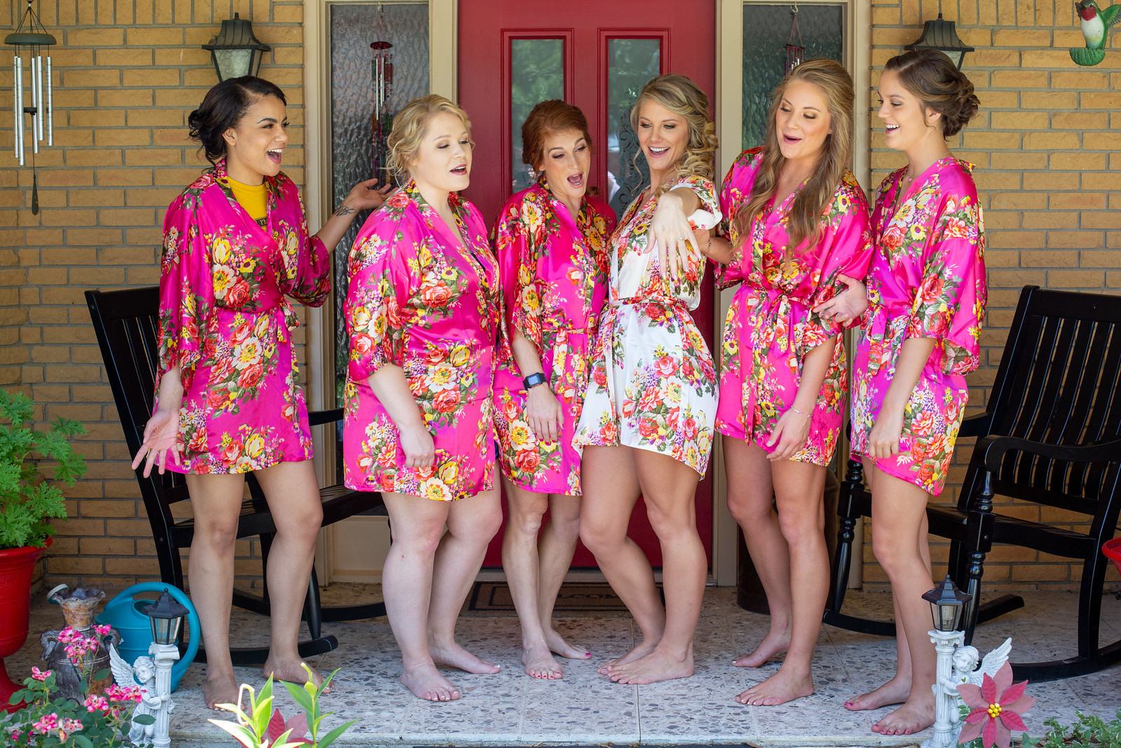 Bridesmaids wearing pink japanese robes as they smile at the bride while she shows off her wedding ring