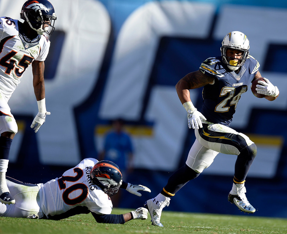 . San Diego Chargers running back Ryan Mathews (24) gets past a diving Denver Broncos strong safety Mike Adams (20) as he picks up a big gain in the second quarter at Qualcomm Stadium. (Photo by John Leyba/The Denver Post)