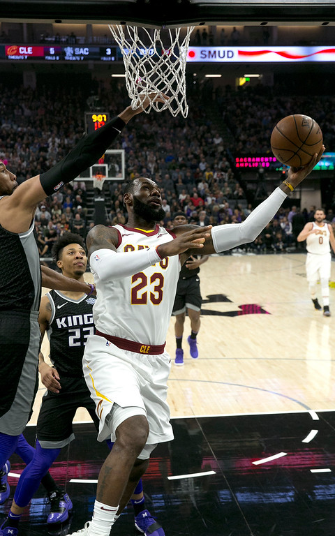 . Cleveland Cavaliers forward LeBron James, right, goes to the basket against Sacramento Kings\' Garrett Temple, left, and Malachi Richardson during the first quarter of an NBA basketball game, Wednesday, Dec. 27, 2017, in Sacramento, Calif. (AP Photo/Rich Pedroncelli)